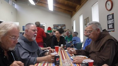 Clergy and parishioners seated together enjoy a pot luck