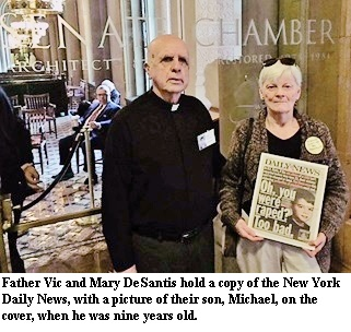Father Vic and Mary DeSantis hold a copy of the New York Daily News, with a picture of their son, Michael, on the cover, when he was nine years old.