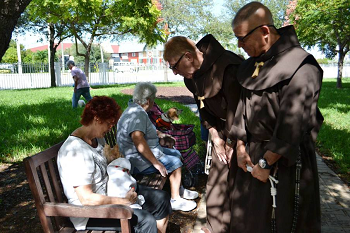 Two Friars standign outside bending down to two seniors seated on a bench
